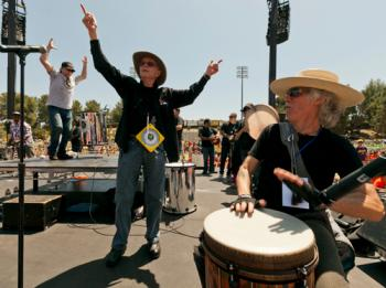 Grateful Dead drummer Mickey Hart, left, Remo Belli, founder and CEO of Remo, Inc., center, and John Densmore, the drummer of the rock group The Doors celebrate as they set the beat of Rock the Rhythm, Beat the Odds, a giant drum circle event.